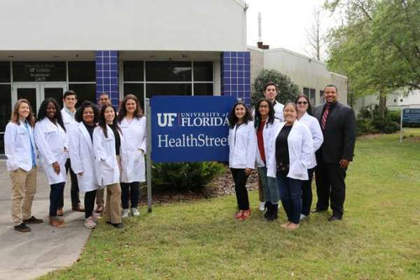 Pictured is Dr. Micah Johnson and the students of the STOMP Lab standing in front of the Health Street sign at UF Health Street